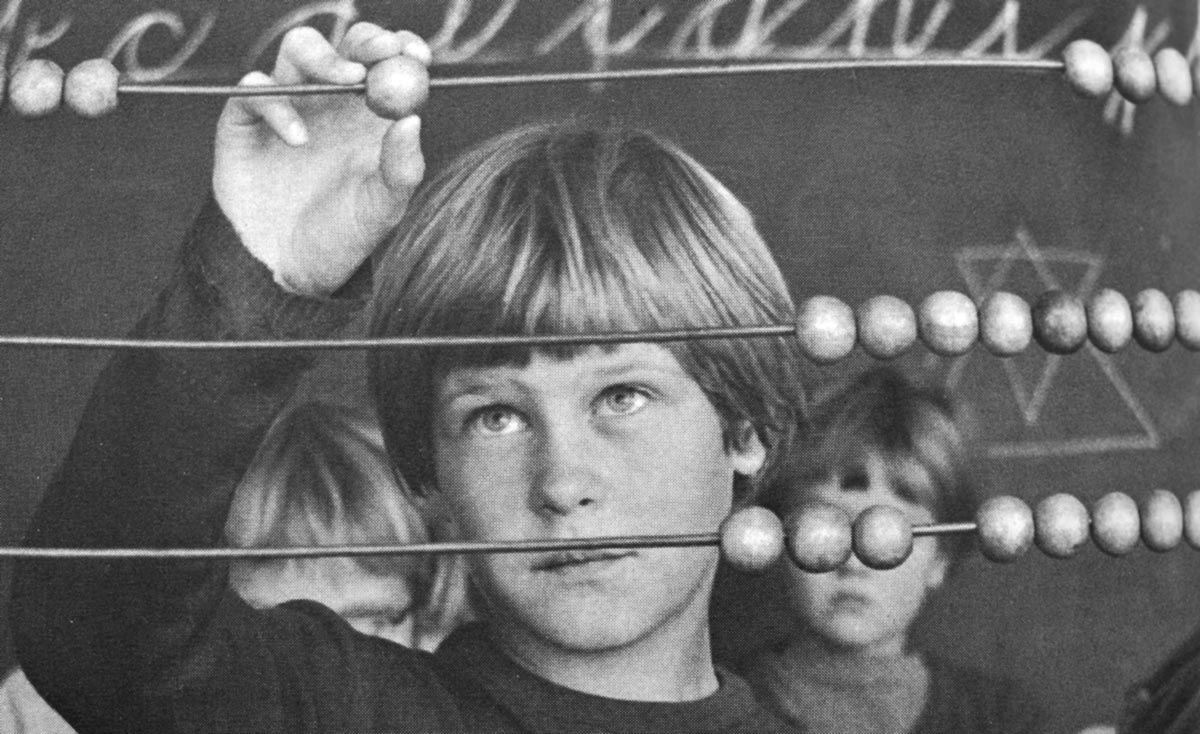 Description: Black and white photo. A boy stands behind a very large abacus that fills the image. He looks up at the ball he is moving on one of the abacus's wires, above his eye-level. Behind him are two schoolchildren and a chalkboard with indistinct writing and diagrams.